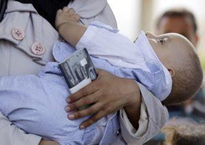 لاجئة سورية تحمل جواز سفر وطفلًا وهي تمر عبر بوابة سيلفيغوزو التركية الحدودية مع سوريا- 30 من آب 2013 (AP)