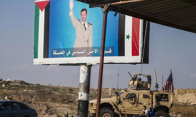 مدرعة أمريكية أمام صورة لرئيس النظام السوري بشار الأسد في القامشلي شمالي سوريا - 26 تشرين الأول 2019 (AP)