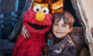طفل سوري لاجئ في الأردن مع دمية برنامج أهلًا سمسم (IRC)