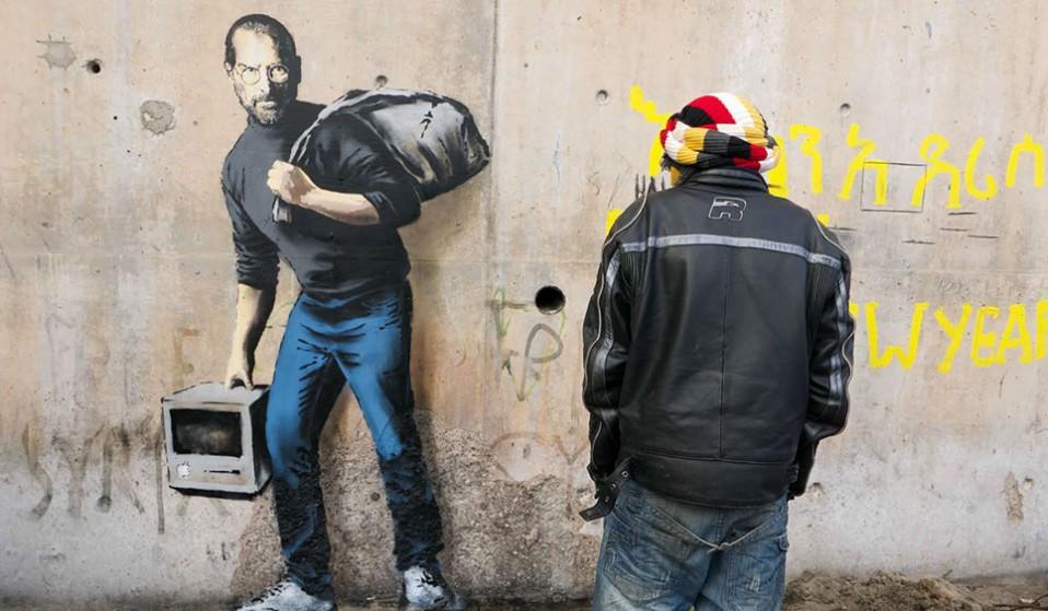 """جدارية """"ابن مهاجر من سوريا"""" للفنان البريطاني بانكسي على حائط مخيم كاليس الفرنسي - كانون الأول 2015 (Banksy)"""
