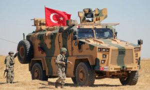 جندي تركي يسير بجوار مركبة عسكرية تركية أثناء دورية مشتركة بين الولايات المتحدة وتركيا بالقرب من تل أبيض ، سوريا 8 أيلول 2019، (رويترز)