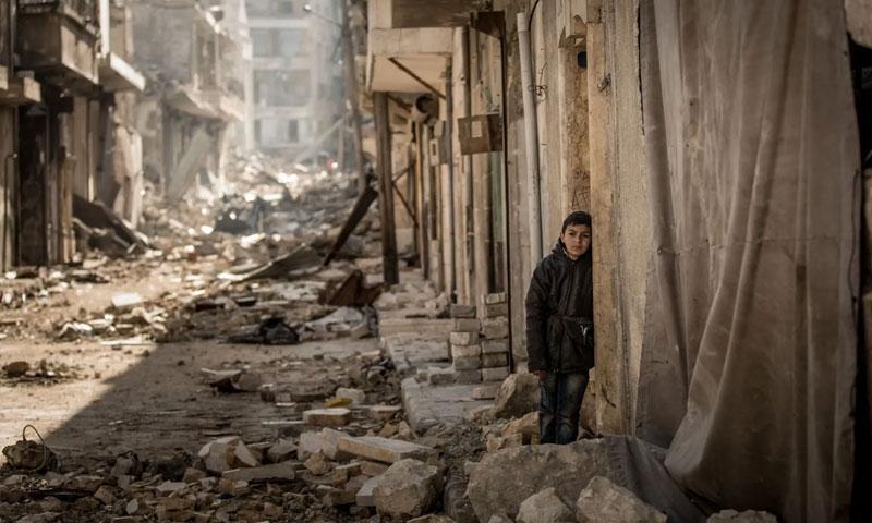 طفل سوري يقف أما بيته المدمر في أحد أحياء مدينة حمص - 13 كانون الأول 2018 (ناشيونال جيوغرافيك)