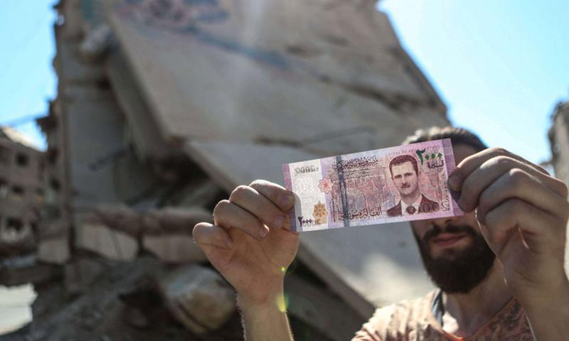 مواطن سوري يحمل فئة نقدية من 2000 ليرة سورية (shutterstock)
