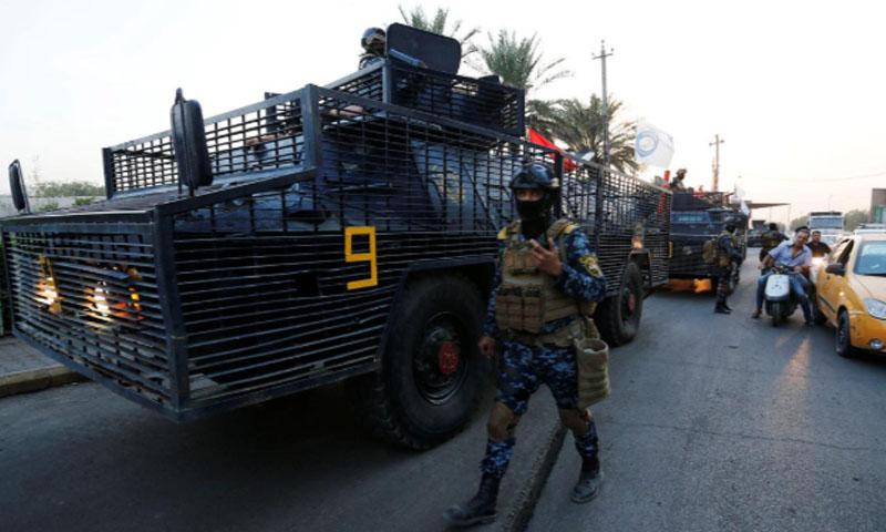 عنصر أمن عراقي بجانب عربة عسكرية تابعة لقوات الشرطة - 7 آب 2019 (رويترز)