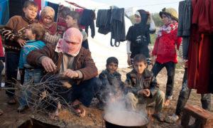 نازحون سوريون يطهون الطعام في مخيم قاح القريب من الحدود التركية (الأمم المتحدة)