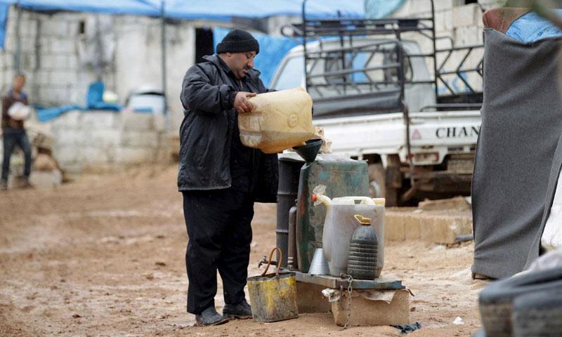 رجل يعبئ الوقود قرب الحدود التركية السورية في محافظة إدلب - كانون الثاني 2019 (MEO)