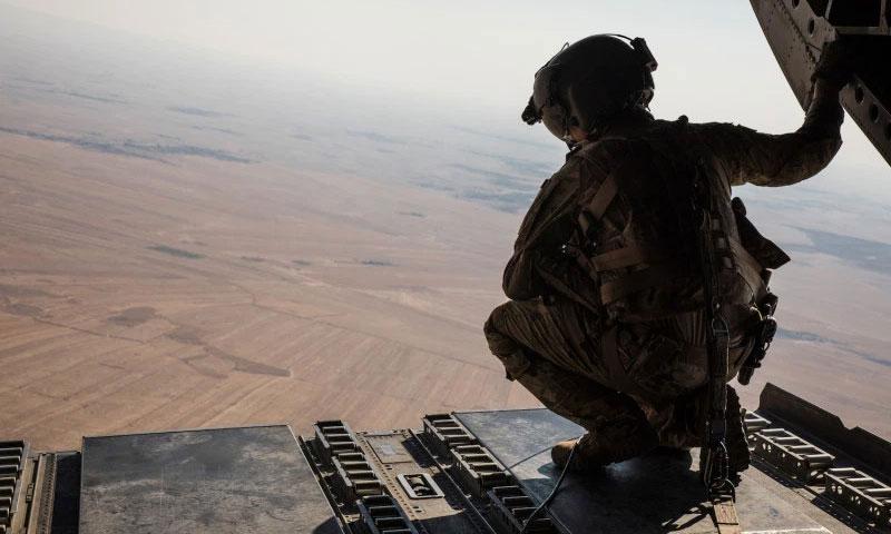 أحد أفراد طاقم CH-47 من طراز Chinook التابع لقوات التحالف يطل من السماء أثناء مهمة نقل في شمال شرق سوريا - (RAY BOYINGTON/U.S. ARMY)
