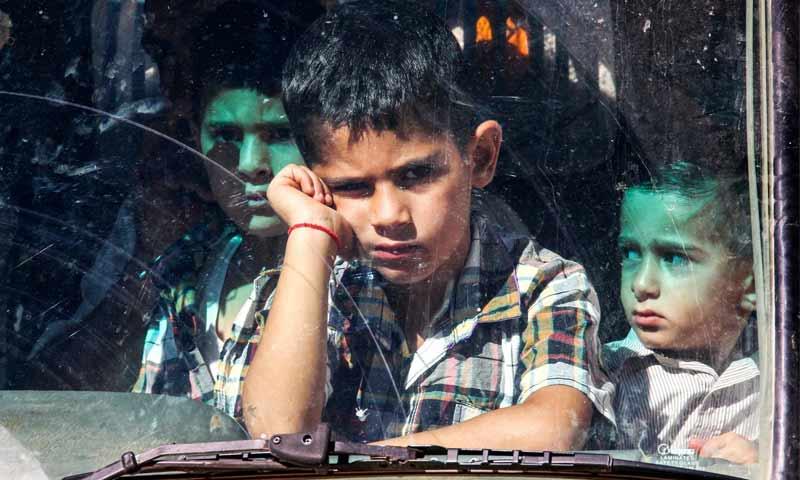 طفل سوري في باص متجه من لبنان إلى سوريا (Getty)
