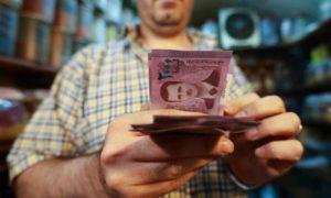 تاجر يعد النقود في سوق البزورية في دمشق - 11 أيلول 2019 (AFP)