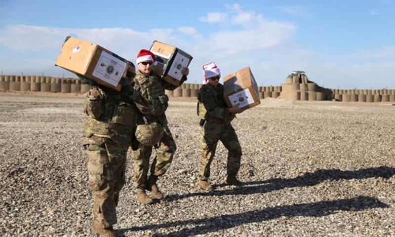 جنود أمريكيون يتلقون هدايا عيد الميلاد بالقرب من حقل العمر النفطي شمال شرقي سوريا -23 كانون الأول 2019 (أسوشيتد برس)