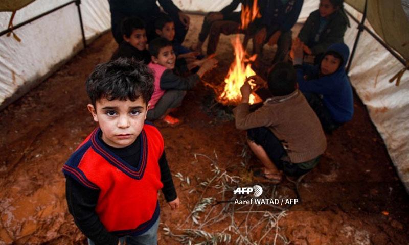 أطفال سوريون داخل خيمة غمرتها مياه الأمطار في مخيم شمالي إدلب -5 كانون الأول 2019- (فرانس برس)