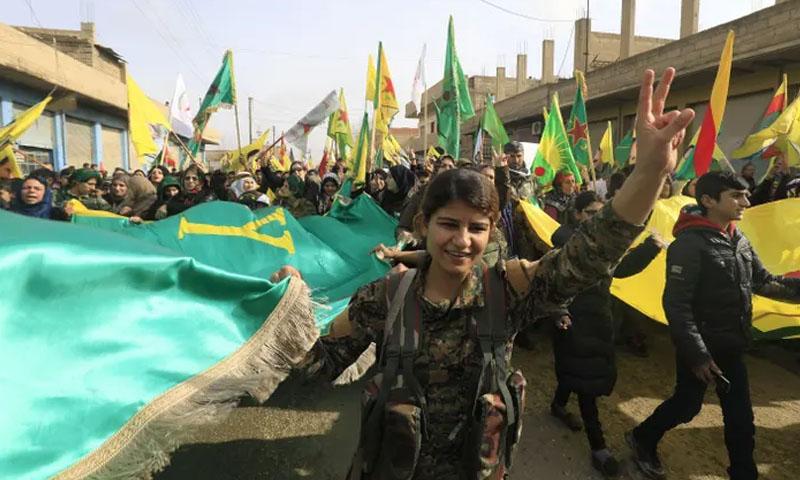 عناصر من وحدات حماية الشعب الكردية خلال مظاهرة في بلدة عامودا شمال شرقي سوريا -كانون الثاني 2018 (فرانس برس)