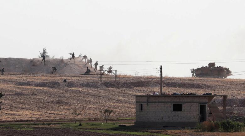 """مقاتلون من """"الجيش الوطني"""" خلال معارك قرية اليابسة شمال شرقي سوريا- 14 من تشرين الأول 2019 (رويترز)"""