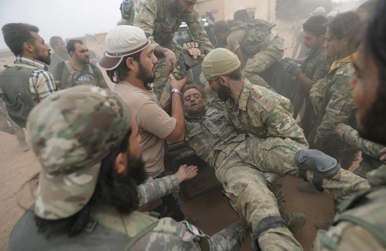 """مقاتبون من """"الجيش الوطني"""" يسعفون زميلهم المصاب في معارك شرق الفرات- 24 من تشرين الأول 2019 (رويترز)"""