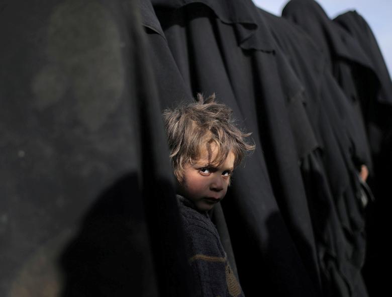 طفل في الباغوز ينظر إلى الكاميرا خلال نزوحه مع أهله- 5 من آذار 2019 (رويترز)