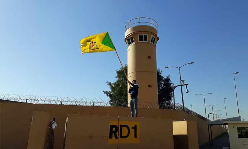 متظاهر يرفع راية كتائب حزب الله العراقي قرب السفارة الأمريكية في بغداد- 31 من كانون الأول 2019 (تويتر)