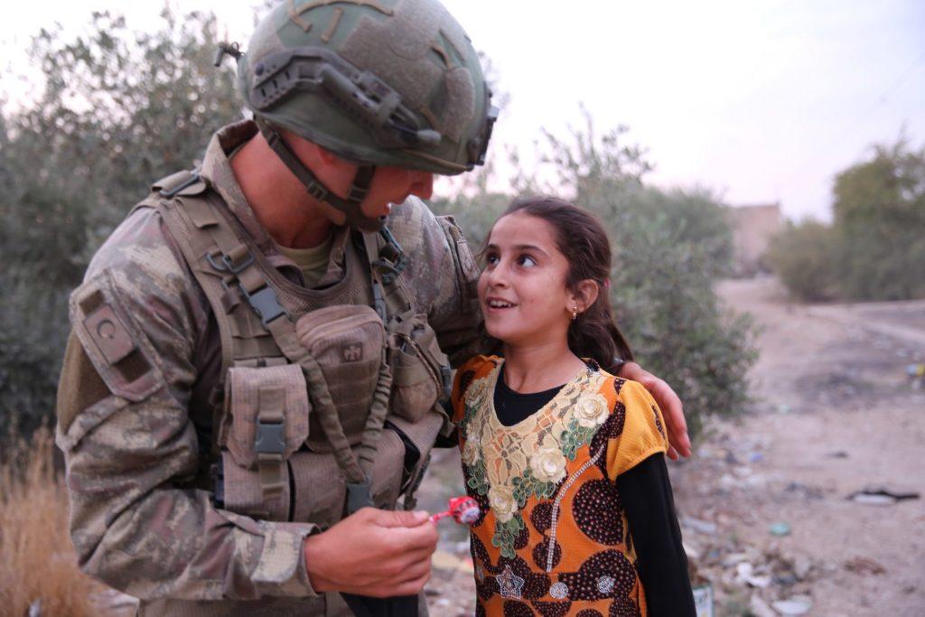 جندي تركي يقدم لطفلة سورية قطعة من الشوكولا في منطقة تل خلف غرب مدينة رأس العين (الأناضول)