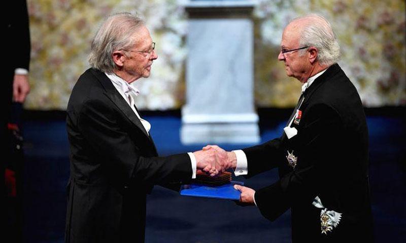 الكاتب النمساوي بيتر هاندك يصافح ملك السويد كارل جوستاف أثناء حصوله على جائزة نوبل لعام 2019 خلال حفل توزيع جوائز نوبل في قاعة ستوكهولم للحفلات الموسيقية في ستوكهولم السويدية - 10 كانون الأول 2019 (رويترز)