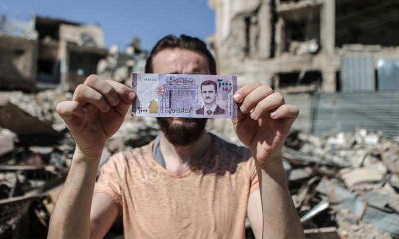رجل سوري يحمل أوراق نقدية من فئة ألفي ليرة في مدينة دوما شرق دمشق - 2017 (EPA)