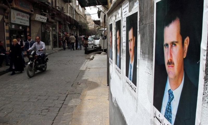 صور لبشار الأسد على جدران مدينة دمشق عام 2000، (FP).