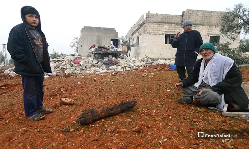 عائلة تجلس أمام منزلها بعد تعرضه للقصف في بلدة كفر تعال بريف حلب الغربي - 20 من كانون الثاني 2020 (عنب بلدي)