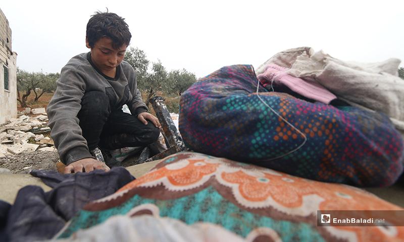 طفل يجمع ما تبقى من أثاث منزله بعد قصفه في بلدة كفر تعال بريف حلب الغربي - 20 من كانون الثاني 2020 (عنب بلدي)