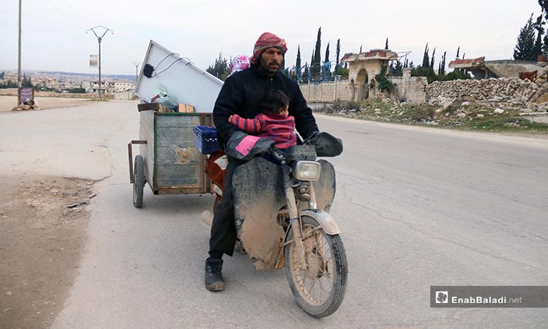 رجل نازح يضع ابنته أمامه بشكل معاكس لحمايتها من البرد في ريف حلب - 16 من كانون الثاني 2020 (عنب بلدي)