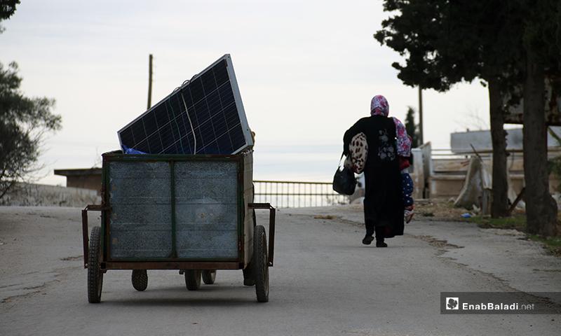 امرأة تركض بعد سماع الطائرات الحربية و الرجل يحاول الخروج على دراجته النارية في محاولة للنزوح من ريف حلب باتجاه الحدود التركية - 16 من كانون الثاني 2020 (عنب بلدي)