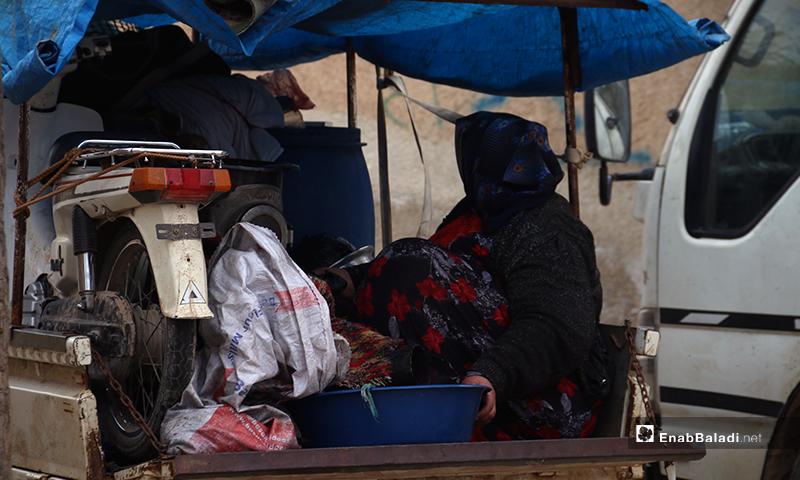 امرأة في مؤخرة سيارة شحن صغيرة تتجه نحو الحدود السورية التركية - 16 من كانون الثاني 2020 (عنب بلدي)