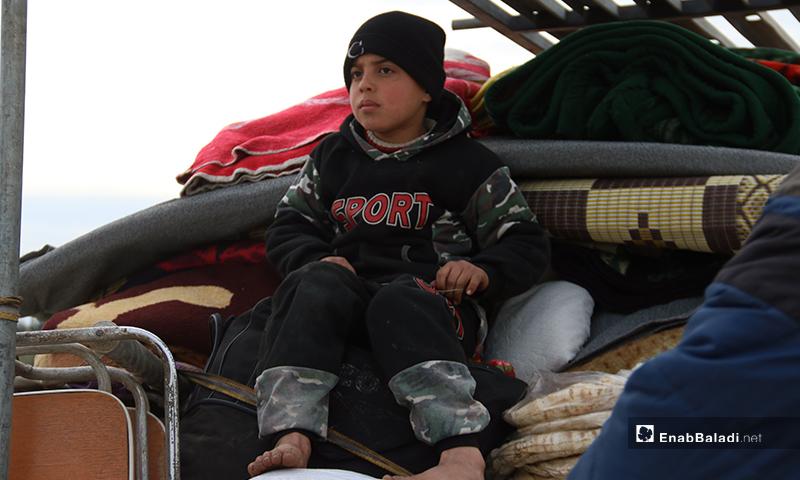 طفل يجلس فوق أثاث منزلهم في سيارة شحن صغيرة تتجه نحو الحدود السورية التركية - 16 من كانون الثاني 2020 (عنب بلدي)