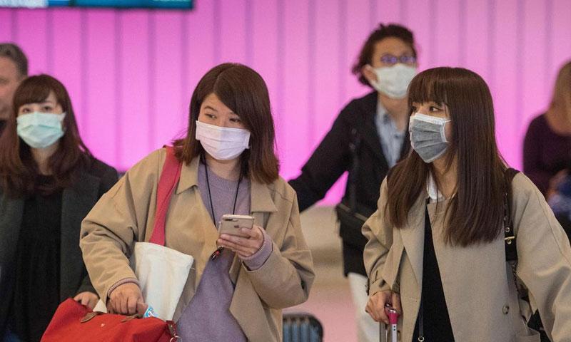 مواطنون صينيون يرتدون الكمامات الطبية للوقاية من فيروس كورونا (CNN)