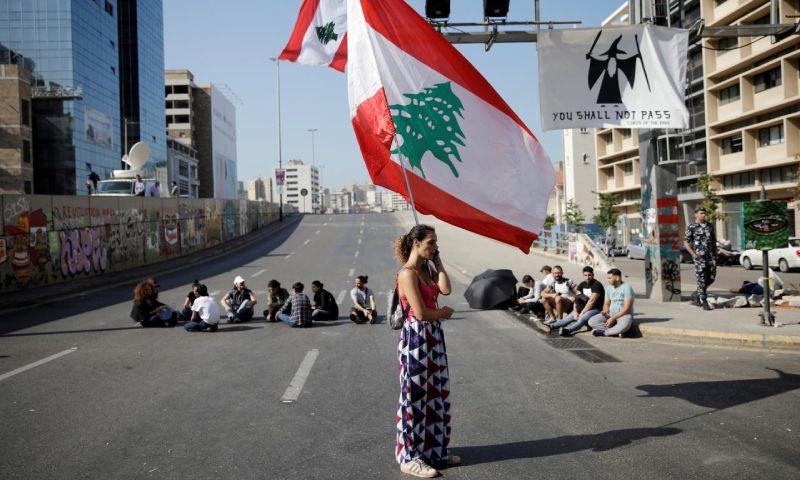 سيدة لبنانية ترفع علم البلاد عند حاجز بشري لمظاهرات مناهضة للحكومة - 4 تشرين الثاني 2019 (رويترز)