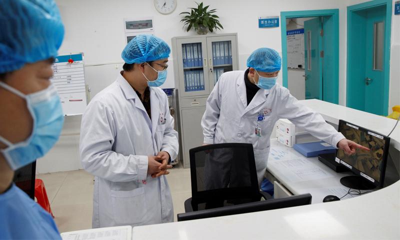 أطباء ينظرون الى شاشة تعرض جناحًا يعالج فيه مصابون بفيروس كورونا الجديد بمستشفى في اقليم هونان بالصين - 27 كانون الثاني 2020 (رويترز)