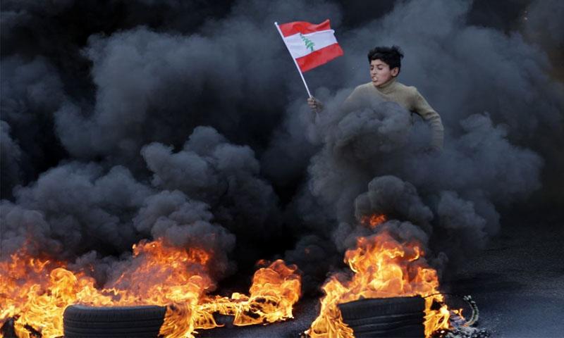 فتى يحمل العلم اللبناني وهو يجتاز دخان إطارات مشتعلة خلا مظاهرات -14 كانون الثاني 2020 (فرانس برس)