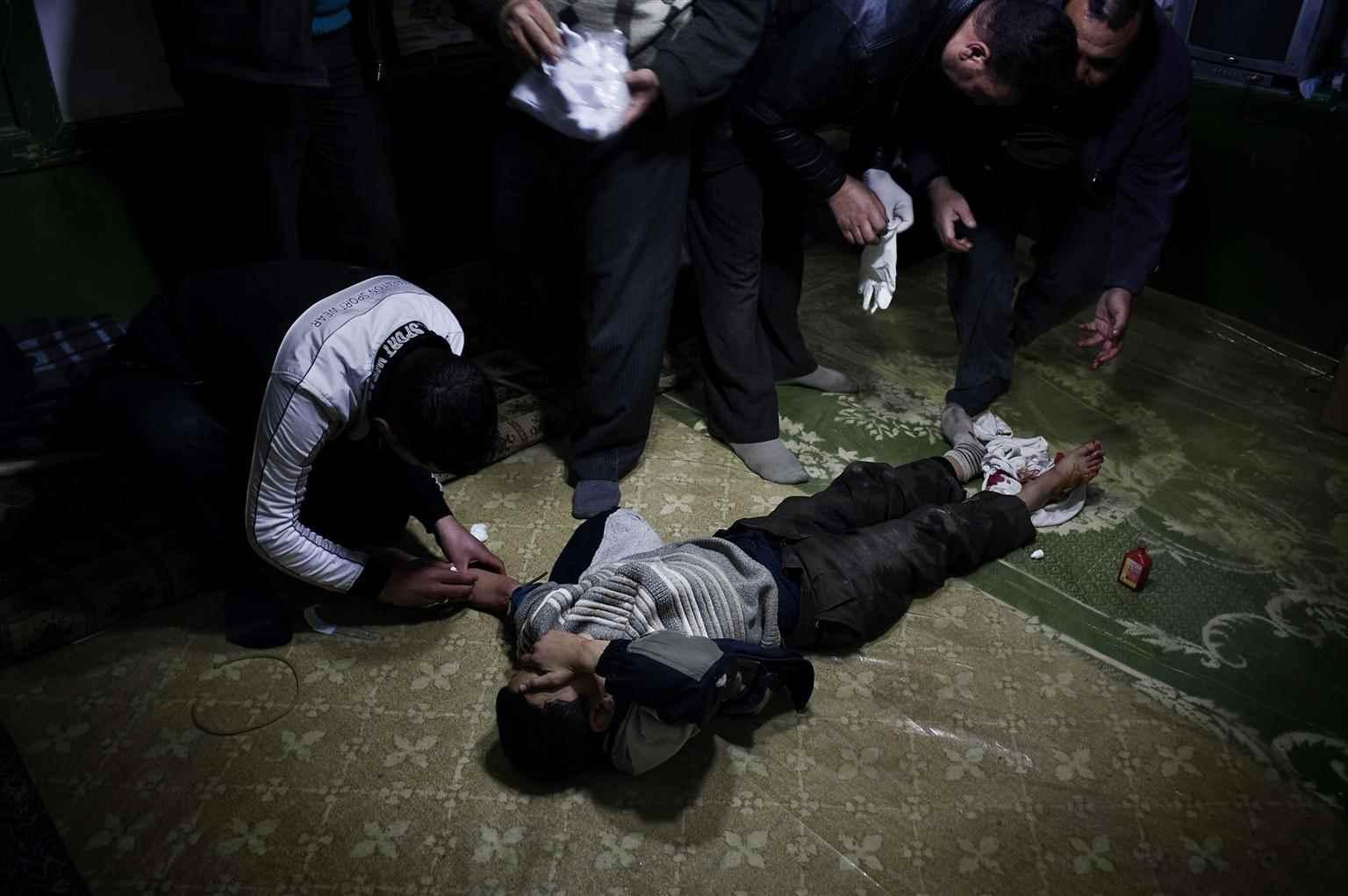طفل يتلقى الإسعافات الأولية بعد أن أصيب بطلق ناري من قبل قناص في سوريا- كانون الثاني عام  2012 (يونيسيف)