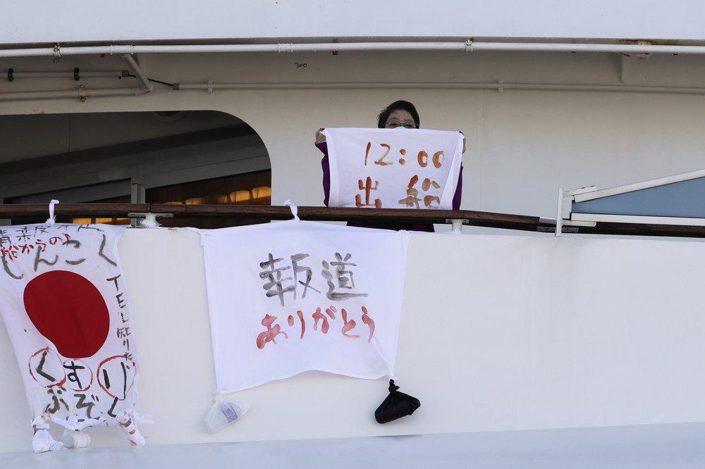 """امرأة تحمل قطعة قماش بسفينة """"The Diamond Princess""""، وقت مغادرة السفينة مكتوبة عليها أثناء الحجر الصحي على متن السفينة في ميناء يوكوهاما بالقرب من طوكيو، """"الحياة على متن سفينة الرحلات الفاخرة، التي تضم عشرات الحالات من فيروس كورونا، يمكن أن تخلق الخوف والإثارة والملل وتملئ النفس-11 من شباط (AP)"""