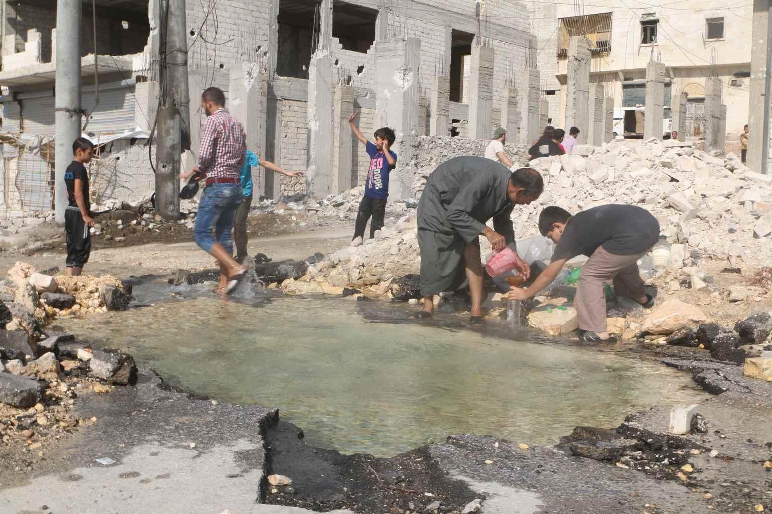 """رجل وصبي يعبئان مياه شرب ملوثة من بركة مياه لحفرة في طريق  بحلب. وبحسب """"يونيسيف"""" اضطر أكثر من 100 ألف طفل في شرق حلب إلى اللجوء للمياه الملوثة بعد أن تعرضت محطة ضخ المياه التي تزود أجزاء من المدينة، لأضرار شديدة جراء المعارك- آب 2016 (يونيسيف)"""
