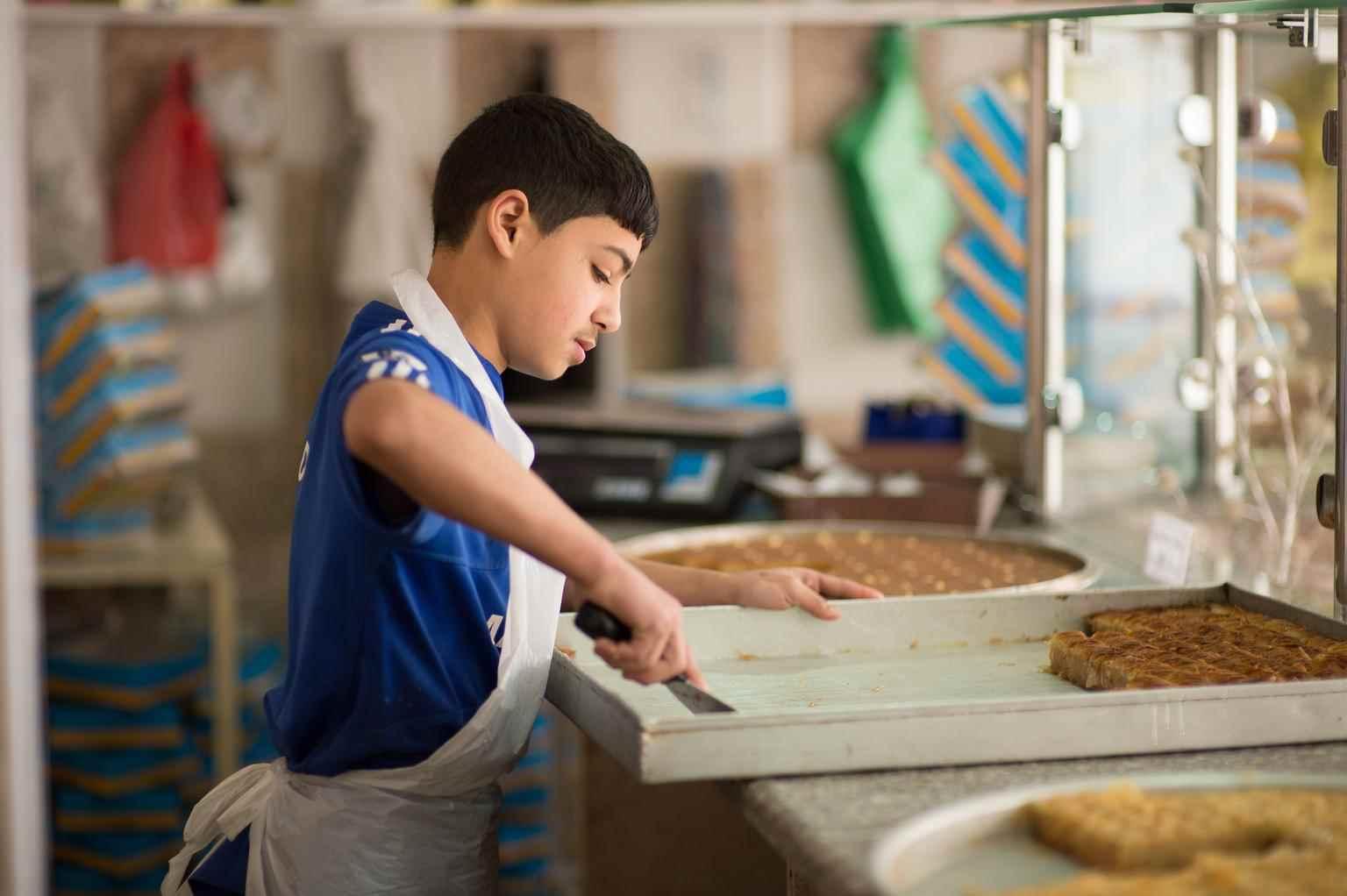 """يقطع محمد، البالغ من العمر 12 عامًا، الحلوى، ويتحدث، """"كنت أدرس في سوريا، وذهبت إلى المدرسة، واعتدت أن أكون قادرًا على الكتابة"""".  ليتابع """"أعمل هنا من الساعة 11:00 حتى 11:00، والدتي مريضة، وكذلك والدي، ولدي خمس أخوات وأنا الابن الوحيد، عندما أعود، لا أرى أحدًا لأنهم يكونوا نائمين، مؤكدًا أنه إذا لم يعمل فلا يوجد من سيساعده هو وعائلته- آذار 2014 الأردن (يونيسيف)"""