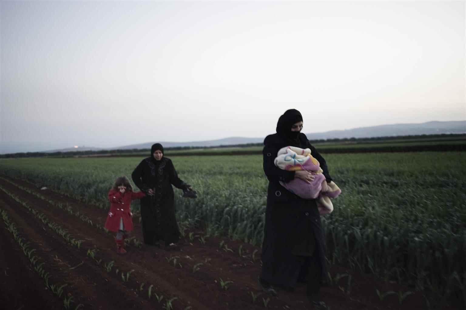 """أطفال ونساء يمشون في حقل محروث أثناء محاولتهم عبور الحدود للجوء إلى تركيا، ووفقًا إلى """"يونيسيف"""" فإنه بحلول تموز 2012، كان مليون و500 ألف شخص ، داخل سوريا في حاجة إلى المساعدة الإنسانية، واليوم وصل هذا الرقم إلى 11 مليون و700 ألف شخص- نيسان 2012 (يونيسيف)"""