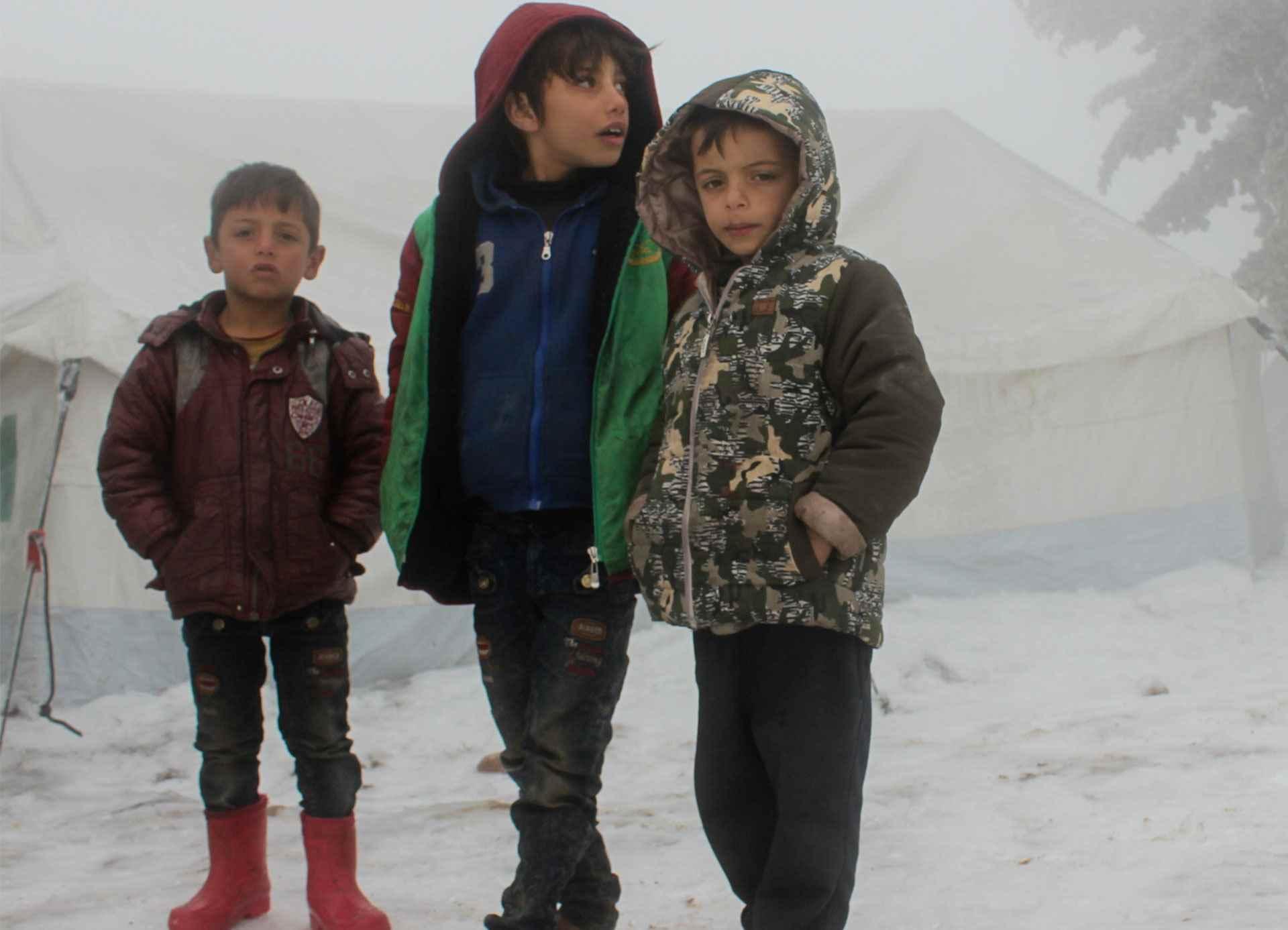 أطفال يقفون معًا في مخيم غير رسمية في سوريا، بالقرب من الحدود التركية. ويضم المخيم حوالي 500 عائلة نازحة من شرق الغوطة وريف إدلب ومحافظات ريف حلب الغربية.  ودفع تصاعد الأعمال العدائية، إلى جانب ظروف الشتاء القاسية وانخفاض درجات الحرارة، علاوة على الوضع الإنساني المتدهور بالفعل، آلاف الأطفال والأسر إلى حافة الهاوية- شباط 2020 (يونيسيف)