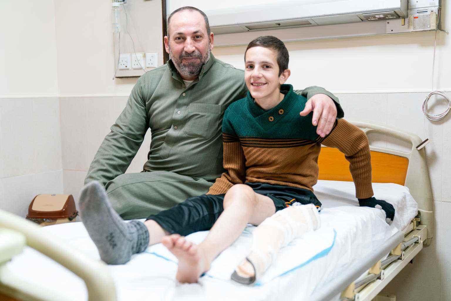 """أصيب أحمد البالغ من العمر 14 عامًا، في سوريا قبل سبع سنوات عندما قصف منزله وانهارت الجدران عليه.  وتقدم """"يونيسف"""" وشركاؤها الرعاية الجراحية لأحمد والأطفال الذين بنفس حالته. وبعد أسبوع واحد من العلاج، بدأ يشعر فعليًا بالأمل، متحدثًا بحماس إلى والده حول الخطوات التالية في حياته أولاً الجراحة ثم مستقبل جديد.  أحمد يقول """"أمنيتي الكبرى هي أن تتحسن، حتى أتمكن من لعب كرة القدم مرة أخرى""""-كانون الثاني 2019 الأردن (يونيسيف)"""