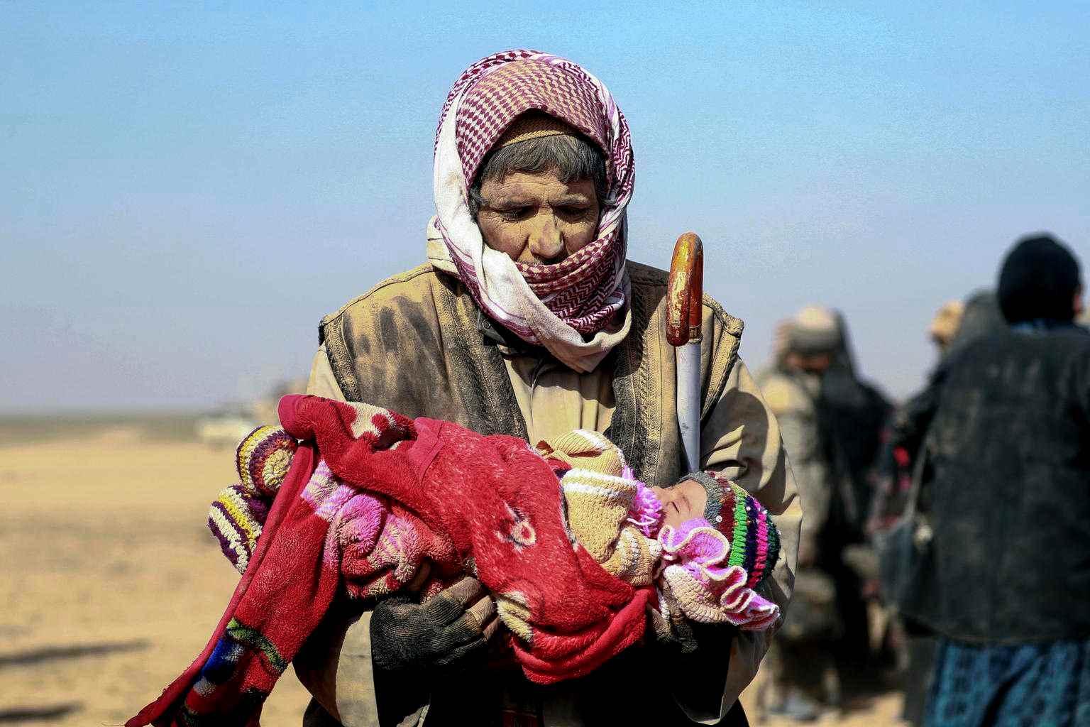رجل يحمل طفلًا عبر الصحراء، أجبر تصاعد العنف الآلاف من الناس على الفرار من منازلهم من أجل سلامة مخيم للمشردين على بعد 300 كم.  إنها رحلة لمدة ثلاثة أيام عبر الصحراء في ظل ظروف الشتاء المتجمدة، مع القليل من الطعام والمأوى على طول الطريق-كانون الثاني 2019  سوريا (يونيسيف)