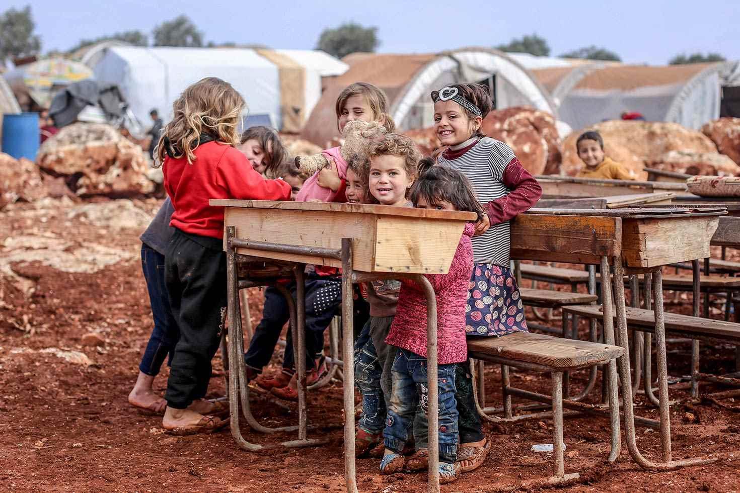 أطفال في مخيم أنشأ مؤخرًا في قرية القح، على بعد حوالي ثلاثة كيلومترات من الحدود السورية التركية، حيث أنشأت العديد من المخيمات الصغيرة غير الرسمية من قبل الأسر، التي تبحث عن الأمان من القصف المتزايد في ريف إدلب الجنوبي- كانون الثاني 2019 (يونيسيف)