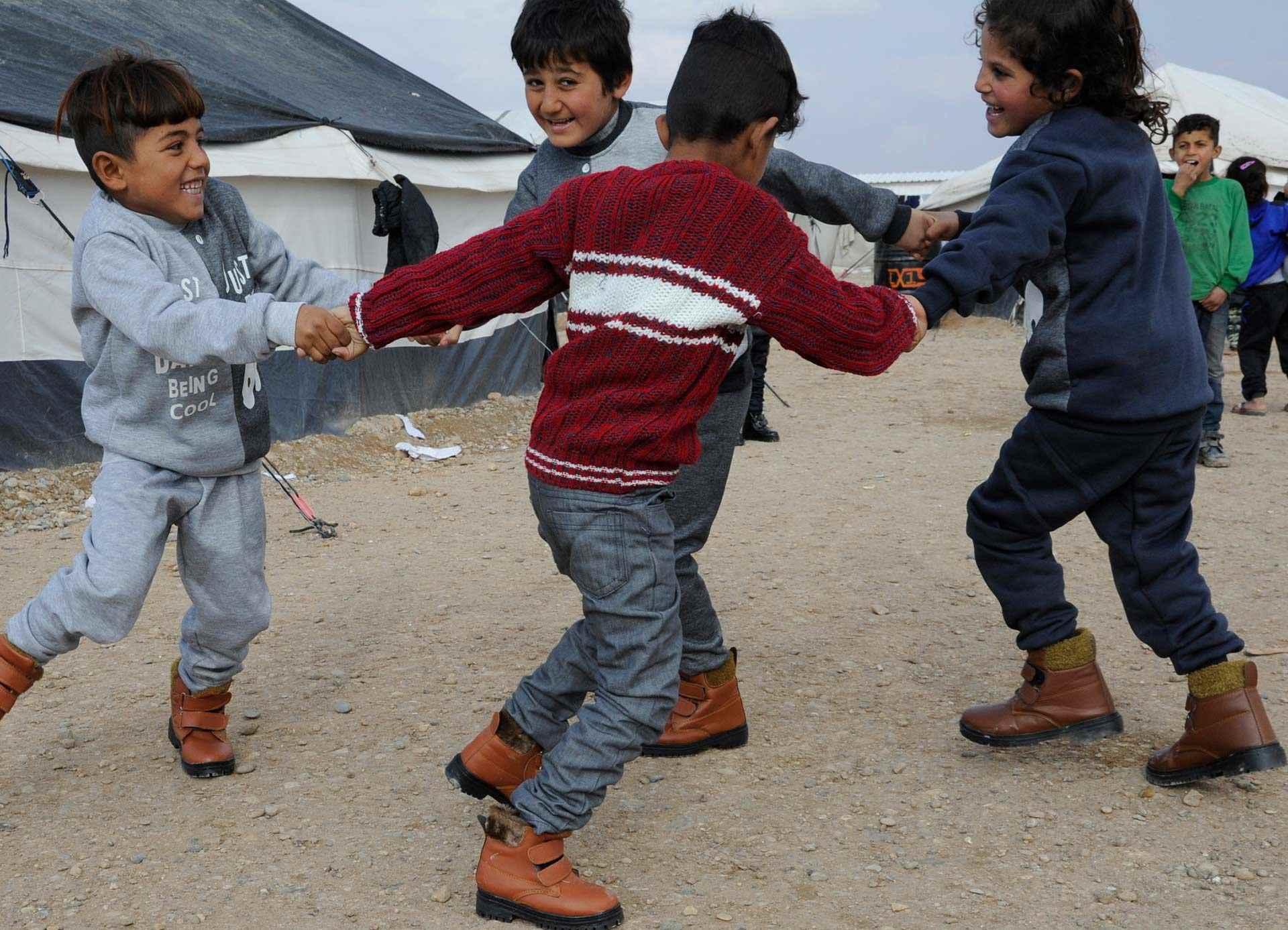 أطفال يلعبون في مخيم بسوريا،  ويواجه  هؤلاء الأطفال والعائلات التي تبحث عن مأوى في المخيمات بمحافظة الرقة فصل الشتاء القاسي.  وأُجبرت  هذه الأسر على الفرار من ديارها بقليل من الملابس على ظهورهم.، لتعيش في مخيمات وسط الصحراء، ولا يوجد شيء لدرء البرد أو الرياح القوية، كما أنه من المألوف هطول أمطار غزيرة لخيام الفيضانات، وتدهور الظروف المعيشية- كانون الثاني 2020 (يونيسيف)