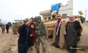 أطفال سوريون يلتقطون صور مع قوات تركية خلال إنشاء نقطة عسكرية جديدة للجيش التركي في بلدة ترمانين شمالي إدلب - 15 شباط 2020 (عنب بلدي)