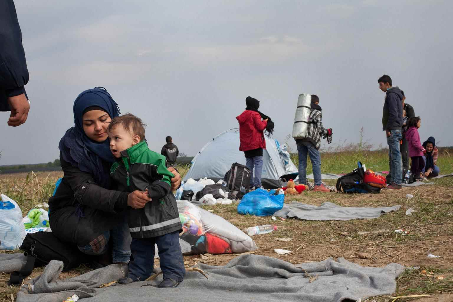 """عبر أكثر من مليون لاجئ ومهاجر إلى أوروبا في عام 2015 بحثًا عن الأمان، من بينهم شيماء، التي في هذه الصورة وهي تستعد لأخيها الصغير يوسف للمرور من مركز عبور في صربيا. """"أنا هنا لاجئة سورية وأذهب إلى ألمانيا لأضع حدًا للمعاناة والألم، يكفي ألمًا، كفي اضطهادًا، لم يعد للفرح مكانًا في قلوبنا، لقد ذهب كل شيء، لقد ذهب بلدنا، هذا هو ألم الشعب السوري المشترك """".  وأكدت شيماء حينها، أنها لا تريد أي شيء من الحياة سوى سقف فوق رؤسهم وحصيرة للجلوس عليها- تشرين الأول 2015 (يونيسيف)"""
