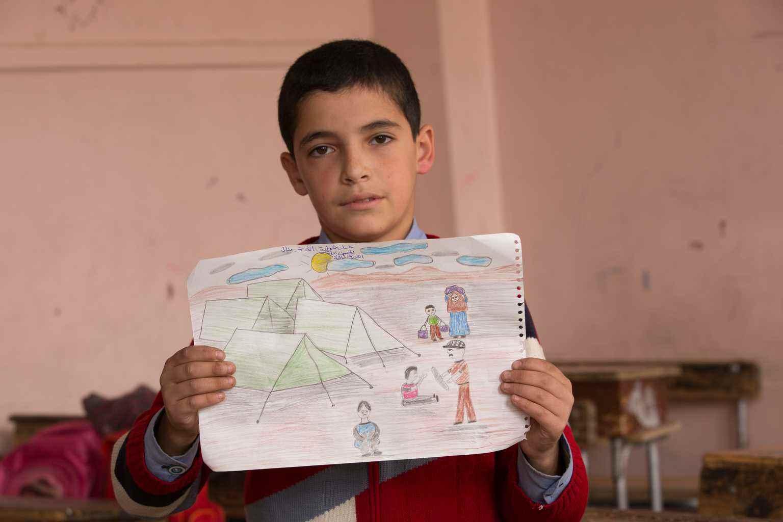 """حسن يحمل صورة لمخيم سوري للاجئين رآه في الأخبار. """"كنت حزينا للغاية عندما رأيت هؤلاء الناس على التلفزيون، ليس لديهم أي شيء""""، ثم نزحت عائلة حسن من مدينة حمص القديمة، والتقطت هذه الصورة قبل خمس سنوات- كانون الأول 2016 (يونيسيف)"""