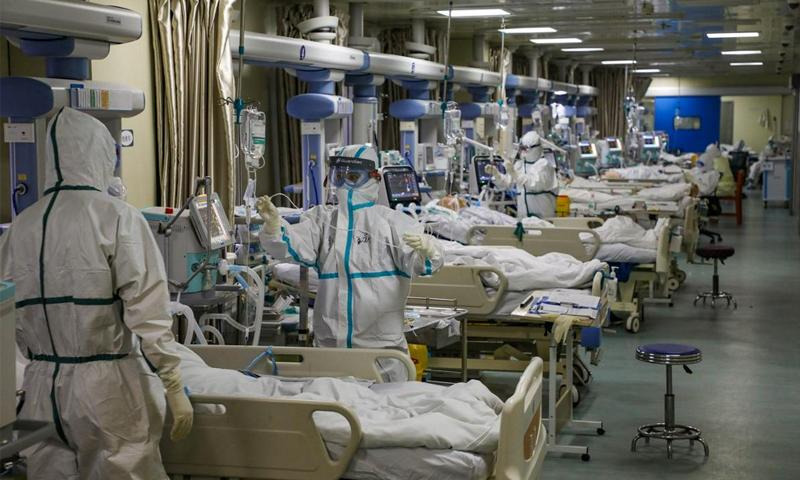 أطباء وممرضون في ملابس وقائية يعالجون مرضى فيروس كورونا الجديد في مستشفى في ووهان بالصين- 6 من شباط (رويترز)