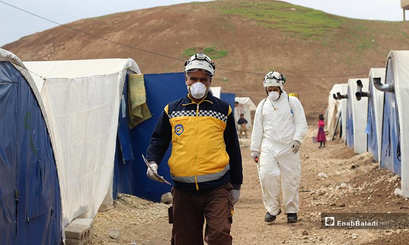 """عناصر الدفاع المدني داخل مخيم بلدة دابق شمالي حلب للبدء بتعقيمه من فيروس """"كورونا""""- 29 من آذار (عنبت بلدي)"""