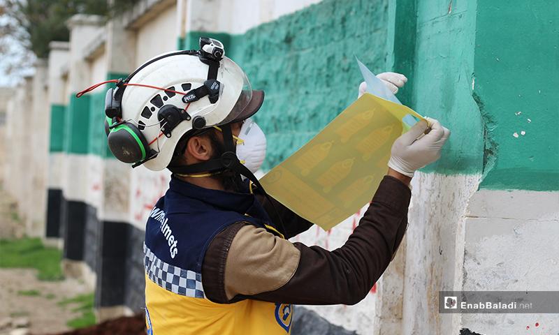 """أحد العناصر وهو يعلق المنشورات التوعوية حول فيروس """"كورونا"""" على جدران بلدة دابق بريف حلب الشمالي- 29 من آذار (عنب بلدي)"""